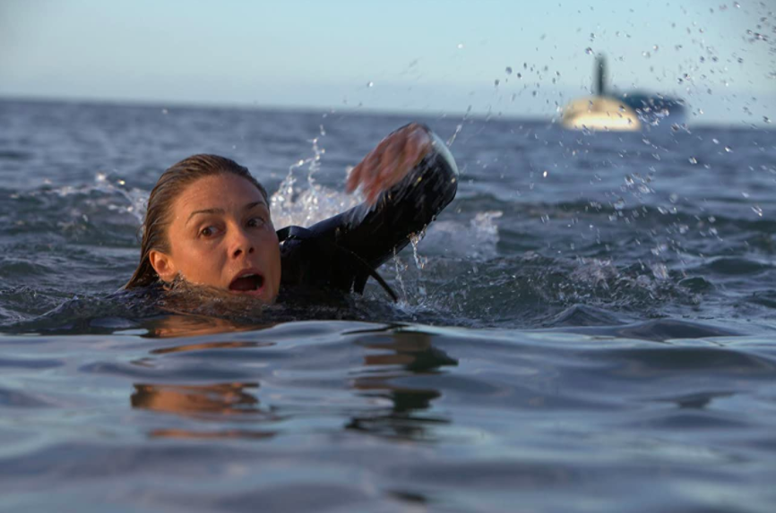 woman swimming away from a shark